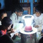 Children sitting around a solar lamp